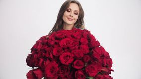 Attractive woman going to camera with bouquet of red roses