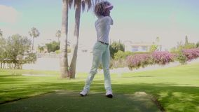 Attractive woman golfer playing a shot stock video footage