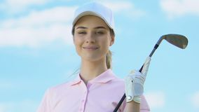 Attractive woman in golfer uniform and with club posing to camera, luxury hobby. Stock footage stock video
