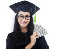 Attractive woman in graduation gown holding money Royalty Free Stock Photography