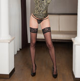Attractive woman in green corset and stockings posing challenging. In room. Sensual woman with long legs and high heels in corset and bikini. Classic boudoir royalty free stock photography