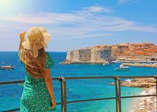 Attractive woman with green dress enjoys the view of the old town of Dubrovnik, Croatia royalty free stock photo