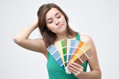 Attractive woman in green t-shirt chooses a color scheme. royalty free stock photo
