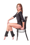 Attractive woman in gym suit sits on chair Stock Images