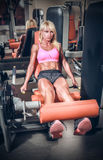 Attractive woman in gym on workout machine Stock Photography