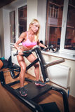 Attractive woman in gym on workout machine Royalty Free Stock Photos