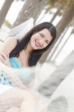 Attractive woman in a hammock. A beautiful young woman sitting in a hammock outdoors Royalty Free Stock Images
