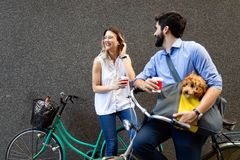 Happy young couple spending time together with dog and bicycles. Attractive women and handsome men spending time together with dog and bicycles royalty free stock image