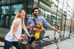 Happy young couple spending time together with dog and bicycles. Attractive women and handsome men spending time together with dog and bicycles stock photos