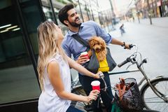 Happy young couple spending time together with dog and bicycles. Attractive women and handsome men spending time together with dog and bicycles stock images