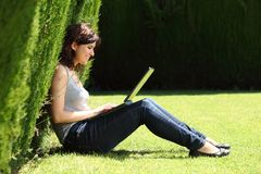 Attractive woman happy in a park with a laptop Royalty Free Stock Photo