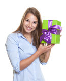 Attractive woman has a gift with ribbon in her hand Stock Photography