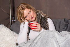 Attractive woman has a warming drink in her hand Royalty Free Stock Photography