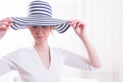Attractive woman with hat in armchair Stock Photography