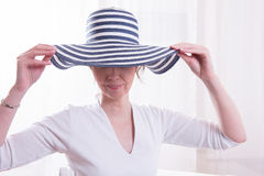 Attractive woman with hat in armchair Stock Photos