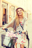 Attractive woman in hat with bicycle in the city Stock Photography