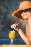 Attractive woman in hat with glass of orange juice Royalty Free Stock Photos