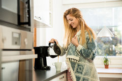 Attractive woman having coffee. Attractive woman in the kitchen pouring a mug of hot filtered coffee from a glass pot. Having breakfast in the morning Stock Image