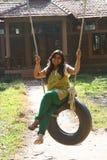 Attractive Woman having fun on tire swing royalty free stock photos