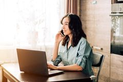 Happy young woman using laptop at home. Attractive woman having happy look while speaking over smartphone, using black laptop. People, technology, lifestyle stock photos