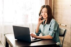Happy young woman using laptop at home. Attractive woman having happy look while speaking over smartphone, using black laptop. People, technology, lifestyle royalty free stock photos