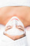 Attractive woman having white cream on her face at spa center Stock Photos