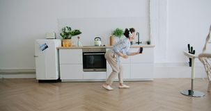Woman in headphones dancing listening to music holding smartphone in kitchen. Attractive woman in headphones is dancing listening to music holding smartphone stock footage