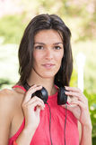 Attractive woman with headphones looking at the camara. Royalty Free Stock Image