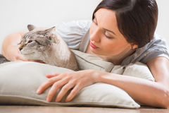 An attractive woman and her cat relaxing on pillows on floor at Stock Image