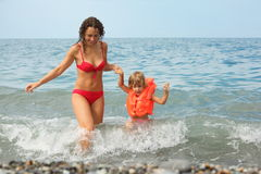 Attractive woman with her daughter in water. Royalty Free Stock Images