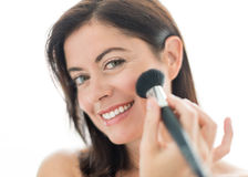 Attractive woman in her forties applying makeup royalty free stock photography