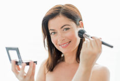 Attractive woman in her forties applying makeup Stock Images