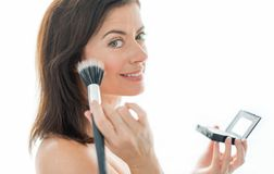 Attractive woman in her forties applying makeup Stock Image