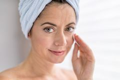 Attractive woman in her forties removing make up Stock Images