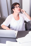 Attractive woman in her home office overworked Stock Photography