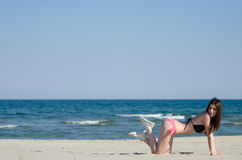 Attractive woman on her knees hands down wear bikini Royalty Free Stock Photos