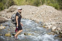 Attractive Woman hiking across a mountain stream royalty free stock images