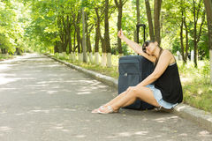Attractive woman hitchhiking. Sitting on the verge on the side of a tree-lined country road thumbing a lift with her suitcase Stock Photos