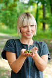 Attractive woman holding acorns outside. Attractive blond woman in nature outside holding acorns Stock Image