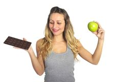 Attractive woman holding apple and chocolate bar in healthy fruit versus sweet junk food dilemma Stock Photo