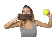Attractive woman holding apple and chocolate bar in healthy fruit versus sweet junk food temptation. Young attractive sport woman holding apple and chocolate bar Royalty Free Stock Images