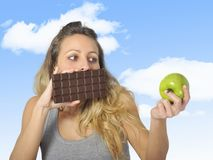 Attractive woman holding apple and chocolate bar in healthy fruit versus sweet junk food temptation. Young attractive sport woman holding apple and chocolate bar Stock Images
