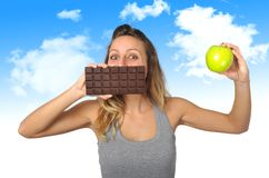 Attractive woman holding apple and chocolate bar in healthy fruit versus sweet junk food temptation. Young attractive sport woman holding apple and chocolate bar Stock Photo