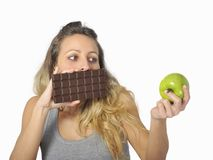 Attractive woman holding apple and chocolate bar in healthy fruit versus sweet junk food temptation. Young attractive sport woman holding apple and chocolate bar Royalty Free Stock Photo