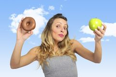Attractive woman holding apple and chocolate donut in healthy fruit versus sweet junk food temptation Stock Photos