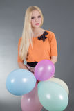 Attractive woman holding balloons over grey Stock Photography