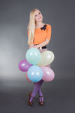 Attractive woman holding balloons over grey Stock Photos