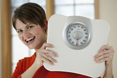 Attractive Woman Holding a Bathroom Scale Stock Photography