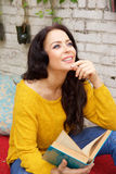 Attractive woman holding book and smiling Royalty Free Stock Image