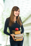 Attractive woman holding books. Attractive student woman holding books and apple Royalty Free Stock Photography
